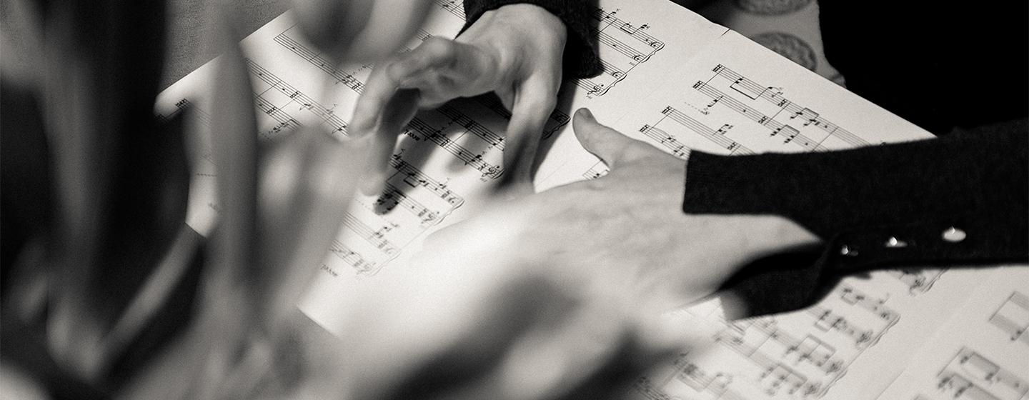 Open Sheet Music Display Background Image: Hands over Sheet Music